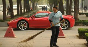 A woman sweeps leaves in front of a new Ferrari 458 Italia in Beijing. Photograph: Peter Parks/AFP/Getty Images