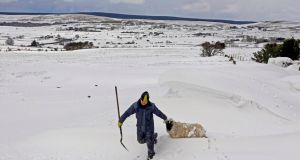 Farmer Donald O'Reilly rescues a sheep trapped in a snow drift in the Aughafatten area of Co Antrim last week. Photograph:  Cathal McNaughton/Reuters