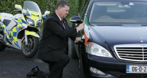 Garda driver Gerry Buttner fixes the Tricolour to the presidential car. Photograph: Frank Miller