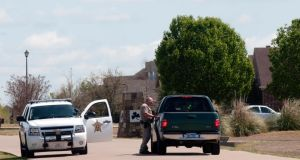 A Kaufman County Sheriff's deputy stops a vehicle entering the neighborhood where Kaufman County District Attorney Mike McLelland and his wife were found dead on SaturdayPhotograph:  C Curry/The New York Times