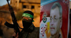 A Hamas militant holds a poster of Maysara Abu Hamdiya before a protest in the northern Gaza Strip yesterday. Photograph: Suhaib Salem/Reuters