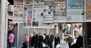 People withdrawing their savings recently from a Laiki bank machine in Athens, while newspapers bear headlines about the Cypriot crisis.  Photograph: Louisa Gouliamaki