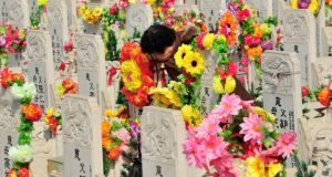 A woman  at the tombstone of a deceased relative at a public cemetery a day ahead of the Qingming Festival, or Tomb Sweeping Day, in Shenyang, Liaoning province, yesterday. Photograph: Reuters