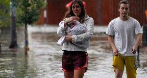 People wade through a flooded street after a rainstorm in Buenos Aires. Record flash floods in Argentina have killed at least 54 people this week, officials have confirmed. Photograph: Enrique Marcarian/Reuters