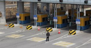 A  South Korea security guard stands on the empty road connection Kaesong Industrial Complex (KIC) with South's CIQ (Customs, Immigration, Quarantine) at inter-Korean transit office this morning in Paju, South Korea. Photograph: Chung Sung-Jun/Getty Images