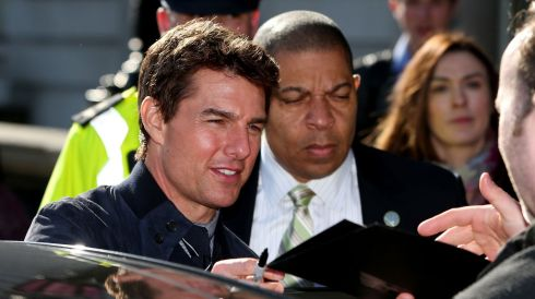 Tom Cruise is minded carefully while signing autographs outside the Department of Foreign Affairs in Dublin. He is visiting the capital for the premiere of his latest film, Oblivion. Photograph: Julien Behal/PA Wire