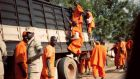 "The ""genocidaires"" dressed in orange: prisoners convicted for crimes of genocide who are now engaged in community work. Photograph: Deirdre McQuillan"