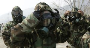 Soldiers of the US army 23rd chemical battalion check their gas masks for a demonstration of their equipment during a ceremony at Camp Stanley in Uijeongbu, north of Seoul, South Korea, yesterday. Photograph: Lee Jin-man/AP