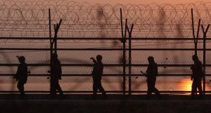 South Korean soldiers patrol inside the barbed-wire fence near the border village of Panmunjom yesterday in Paju, South Korea. North Korea seems to be following its usual strategy of using belligerent language to win concessions on aid and, ultimately, achieve a peace treaty with the US. Photograph: Chung Sung-Jun/Getty