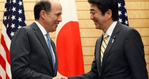 Japan's prime minister Shinzo Abe shakes hands with US ambassador to Japan John Roos as they announce  a US-Japan agreement on the return of some of the US bases in Okinawa in Tokyo today. Photograph: Issei Kato/Reuters