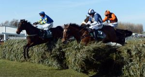 Auroras Encore and Ryan Mania (left) jump into the lead at the final fence on the way to winning the  Grand National. Photograph:   John Giles/PA