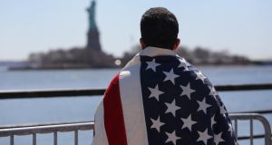 Ecuadorian immigrant Diego Cazar, now living in the US for 12 years, looks towards the Statue of Liberty while participating in a rally for immigration reform at the weekend. Photograph: John Moore Getty Images