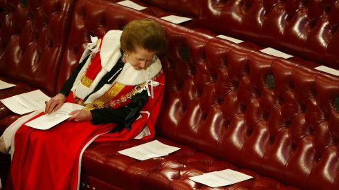 Thatcher reads the order of service surrounded by empty seats as she waits for Queen Elizabeth to deliver her speech in the House of Lords in London in 2002. Photograph: Russell Boyce/Reuters