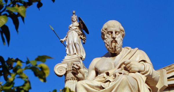 A view of the statues of Socrates in the foreground and Athena on the column in the background, outside the Athens' Academy in the Greek capital