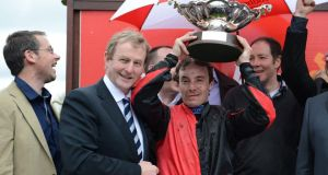 Taoiseach Enda Kenny at Fairyhouse racecourse last year with Grand National-winning  jockey Andrew Thornton.  But has the Government backed the wrong horse in the economy stakes? Photograph: Cyril Byrne