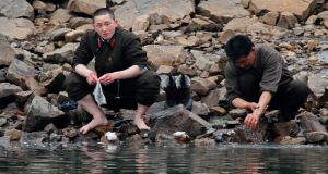 A North Korean soldier washes his socks as his comrade washes his hands at the banks of Yalu River, near the North Korean town of Sinuiju, opposite the Chinese border city of Dandong