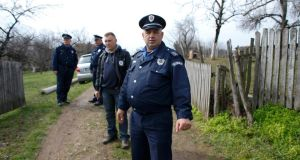 Police officers pictured  in the village of Velika Ivanca, about 40km southwest of Belgrade, where a gunman shot dead   13 people, including his mother and son, in an early-morning rampage today. Photograph: Marko Djurica/Reuters