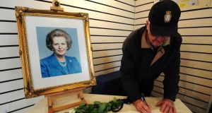 A member of the public signs a book of condolence under a portrait of former prime minister Margaret Thatcher at the Grantham Museum in her hometown Grantham. Photograph: Rui Vieira/PA Wire