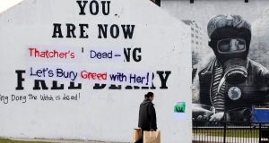 A woman walks past graffiti daubed on the Free Derry Corner in the Bogside area of Derry, Northern Ireland today. Photograph: Cathal McNaughton/Reuters