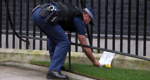 A policeman lays flowers and a tribute outside 10 Downing Street in London, the day after Baroness Thatcher died at the age of 87 following a stroke. Photograph: Steve Parsons/PA Wire