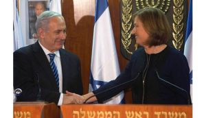Israel's prime minister Benjamin Netanyahu shakes hands with former foreign minister Tzipi Livni, head of the centrist Hatenuah party, during their joint statement at the Knesset, the Israeli parliament last night. Photograph: Reuters