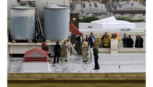 Authorities stand on the rooftop of the Cecil Hotel after a body was found in a water tank in Los Angeles, California, on Tuesday. Photograph: Jonathan Alcorn/Reuters