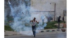 A protester throws back a tear gas canister fired by Israeli troops during clashes outside Israel's Ofer military prison near the West Bank city of Ramallah today. Photograph: Mohamad Torokman/Reuters