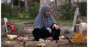 A woman mourns at the grave of her 17-year-old son, who was killed during clashes with forces loyal to Syrian President Bashar al-Assad, in Deir el-Zor yesterday. Photograph: Khalil Ashawi/Reuters