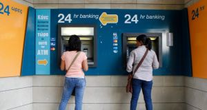 Women withdraw money from ATMs at a branch of the Bank of Cyprus at Eleftheria square in Nicosia late last month. Major depositors in Cyprus's biggest bank will lose around 60 percent of savings over €100,000, its central bank confirmed on Saturday.