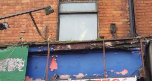 A member of the Save Moore Street campaign stands at the upstairs window of Number 15 Moore Street. Photograph: Éanna Ó Caollaí/The Irish Times
