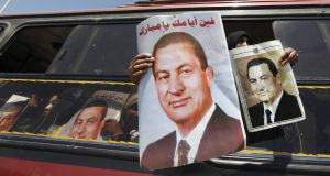 A supporter of Egypt's former president Hosni Mubarak holds pictures during a protest against Egyptian president Mohamed Mursi and members of the Muslim Brotherhood, on a bus after Mubarak's trial outside the police academy in Cairo today. Photograph: Amr Abdallah Dalsh/Reuters.