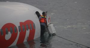 A rescue worker stands at the door of the Lion Air plane. Photograph: Reuters/Indonesian Police Handout.