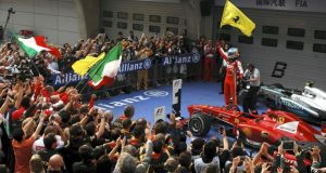 Ferrari Formula One driver Fernando Alonso of Spain waves the team flag as he stands on top of his car to celebrate his win at the Chinese F1 Grand Prix at the Shanghai International Circuit. Photograph: Reuters