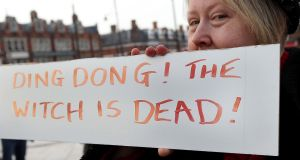 A woman poses behind a sign displaying the message 'Ding Dong! The Witch is Dead!' as she celebrates the death of former British prime minister Margaret Thatcher in Brixton last week. Photograph: Danny E. Martindale/Getty Images