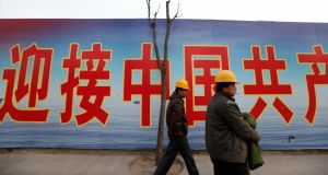 Labourers walk past a banner outside a construction site in Beijing's central business district today.  China's economic recovery unexpectedly stumbled in the first three months of 2013 as the annual rate of growth eased back to 7.7 per cent from the 7.9 per cent pace set in the final quarter of last year. Photograph: Jason Lee/Reuters