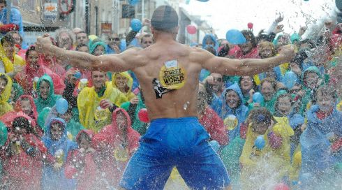 Facing the onslaught: in the midst of a hurricane. Jack Wise, Minister of Silly Ideas and former Street Performance World Championships winner, being pelted with water balloons. Photograph: Dave Meehan/The Irish Times