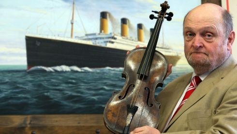 Auctioneer Alan Aldridge with bandleader Wallace Hartley's violin in front of an image of the ill-fated Titanic. Auction house Henry Aldridge & son of Devizes, England states it has gone to great lengths to prove the provenance of the violin, including that it had been immersed in sea water. Today is the 101st anniversary of the sinking of the ship.  The violin and other Titanic-related items are to be auctioned this week. Photograph: Matt Cardy/Getty Images