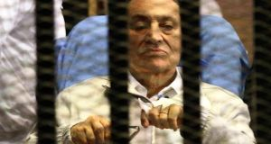 Egypt's deposed president Hosni Mubarak sits inside a dock at the police academy on the outskirts of Cairo April today. Mubarak will stay in detention despite a judge ordering his release on bail pending a retrial over charges in complicity in the murder of protesters because he still faces other charges, court officials have said. Photograph: Stringer/Reuters