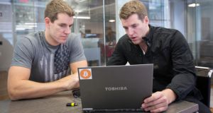 Cameron and Tyler Winklevoss, who have amassed a large bitcoin portfolio, in their office in New York last week. The twin brothers' decision to go public with their position on the digital currency signals a new stage for what has been an experimental alternative to national currencies. Photograph: Agaton Strom/The New York Times