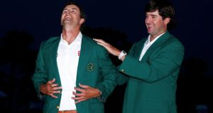 Adam Scott of Australia (left) receives his green jacket from 2012 champion Bubba Watson. Photograph: Mike Segar/Reuters