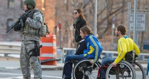 A metro SWAT officer stands guard on Massachusetts Avenue near the scene of multiple bombings near the finish line of the Boston Marathon yesterday. Photograph: Reuters