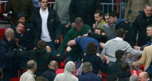 Millwall fans fight during their English FA Cup semi-final soccer match against Wigan Athletic at Wembley Stadium.