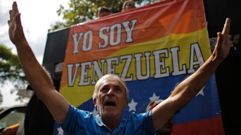 "A supporter of opposition leader Henrique Capriles gestures in front of a banner that reads, ""I am Venezuela"", during a demonstration in front of Capriles's campaign headquarters in Caracas. Photograph: Tomas Bravo/Reuters"