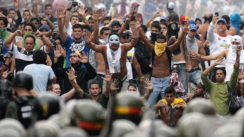 Protesters face off against riot police in Caracas. Photograph: Christian Veron/Reuters