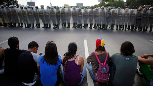 Capriles supporters block a highway in front of riot police. Photograph: Tomas Bravo/Reuters