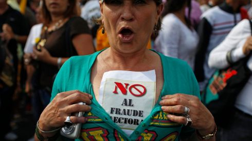 "A supporter of opposition leader Henrique Capriles wears a sign that reads ""No election fraud"". Photograph: Tomas Bravo/Reuters"