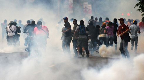 Supporters of opposition leader Henrique Capriles try to get away from tear gas. Photograph: Christian Veron/Reuters