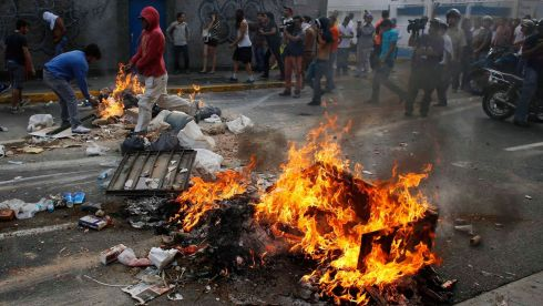 Burning rubbish is used to obstruct streets. Photograph: Tomas Bravo/Reuters