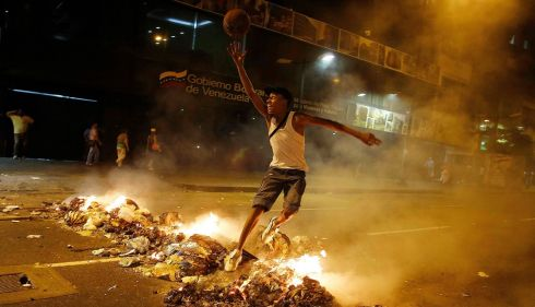 A man plays nonchalantly with a ball amid a barricade of burning rubbish. Photograph: Tomas Bravo/Reuters