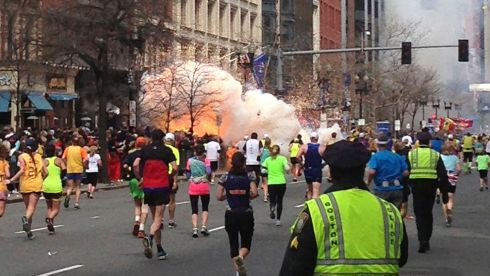 The moment the second blast detonated. Runners continue to run towards the finish line. Photograph: Dan Lampariello/Reuters